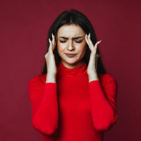 Beautiful brunette caucasian girl dressed in red pullover with painful headache on the pink background